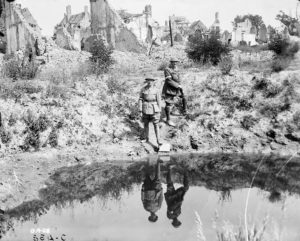 A 17' shell hole in the Main Square, Ypres. Brig.-Gen. Burstall and Captain Papineau. July, 1916. (LAC MIKAN no. 3403747 )